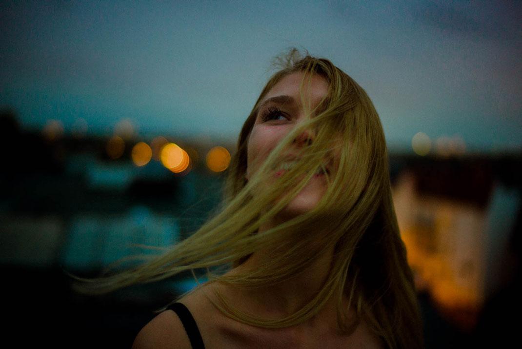 Junge Frau lächelt die Haare wehen im Wind