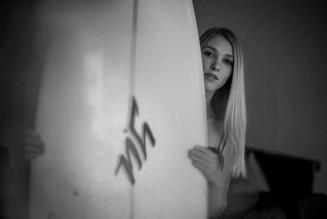 Frau hält ein Surfbrett