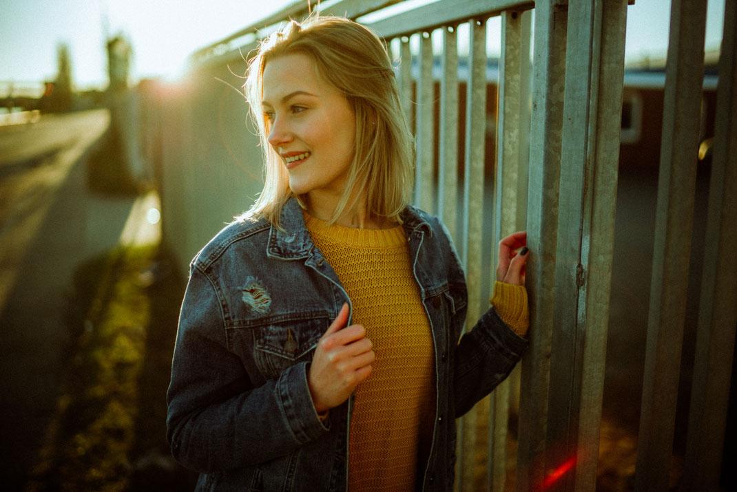 Junge Frau mit Jeansjacke lächelt