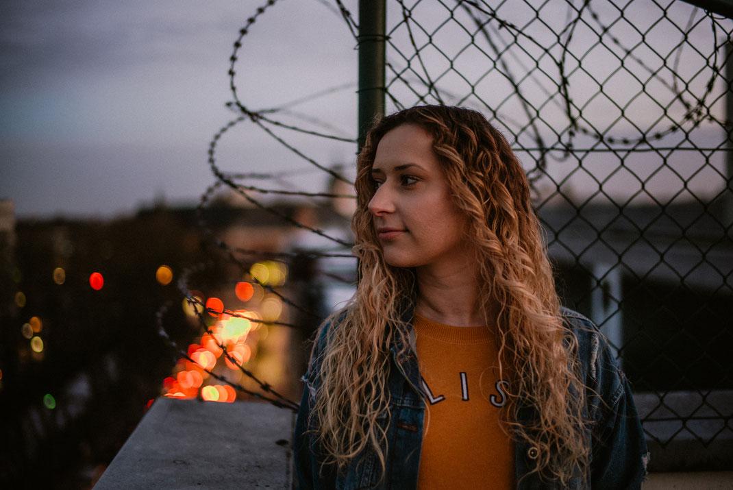 Frau blickt von einem Oldenburger Parkhaus-Dach im Hintergrund Lichter