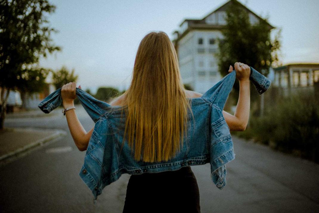 Rückansicht einer Frau mit Jeansjacke