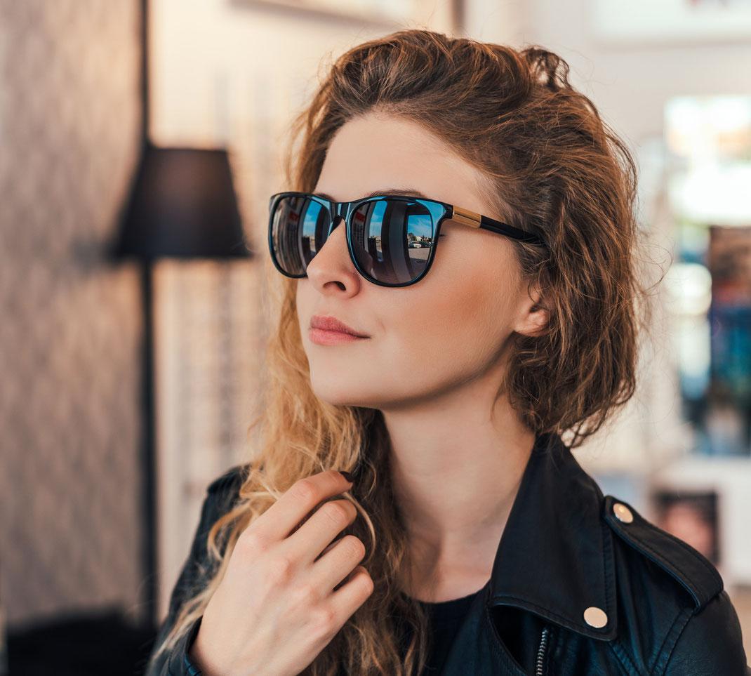 junge Frau kauft modische Sonnenbrille in Berlin