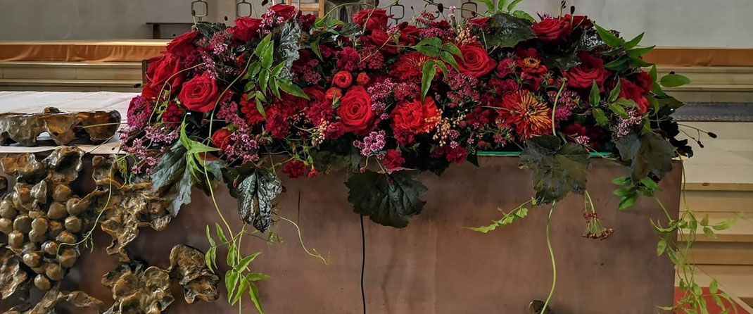 Hochzeits-Altarschmuck mit roten Blumen und grünen Blättern