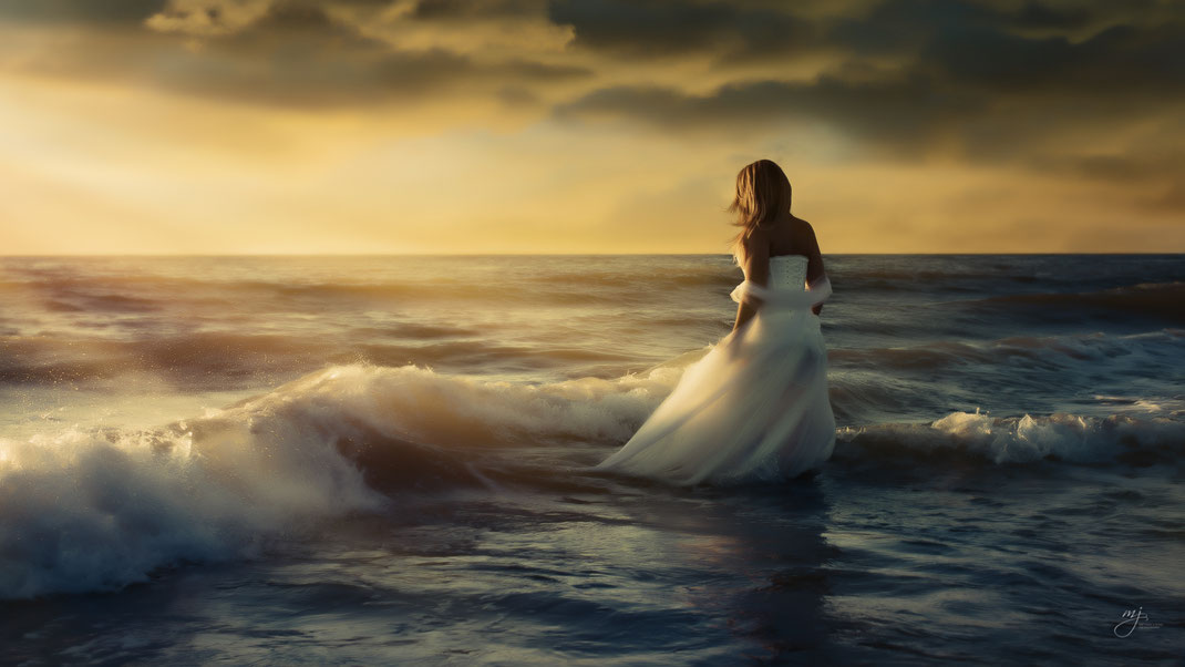 woman in white dress standing in the ocean