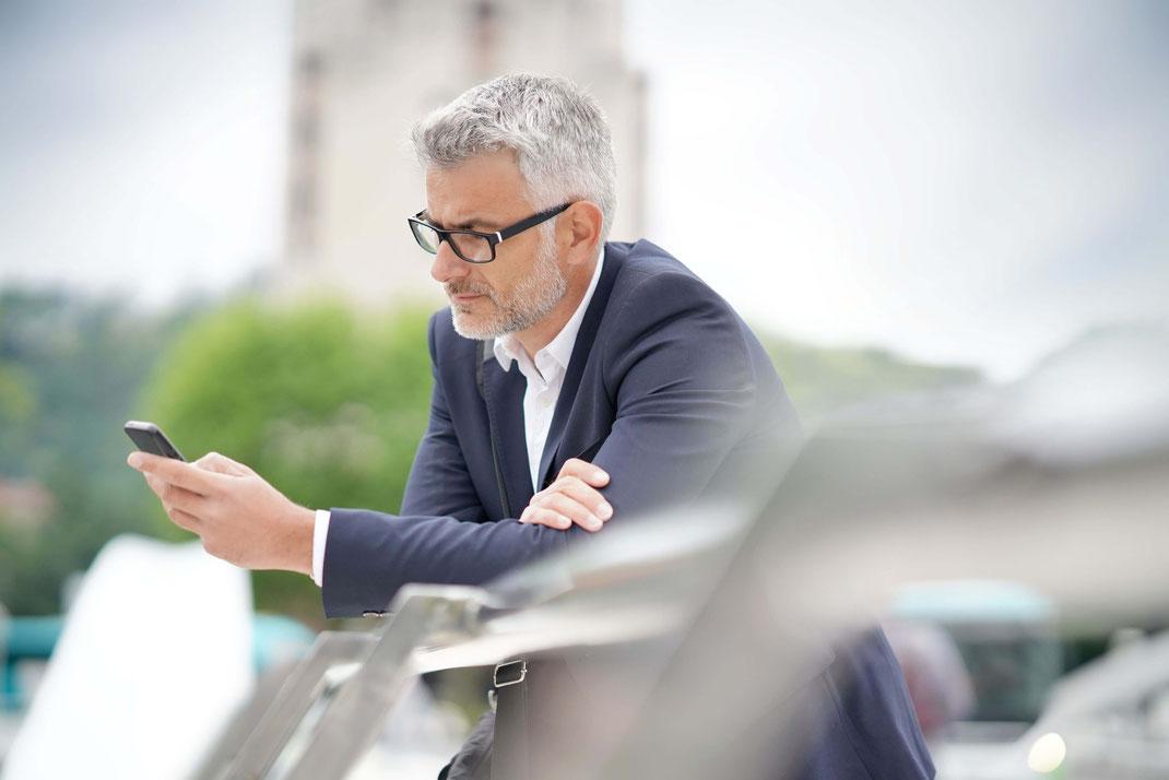 Mann wartend mit Handy und Brille