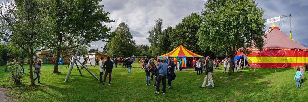 Panoramabild vom Gelände. Zu sehen sind das große und ein kleines Zirkuszelt, die Seilbahn und in Kleingruppen verteiltes Publikum