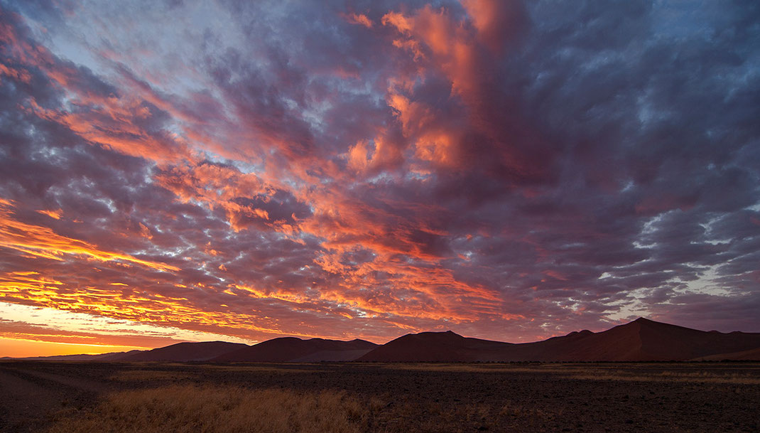 Beautiful sunset in Sossusvlei, Namib Desert with red, purple and orange color with orange sand dunes, Namib Naukluft Park, Namibia, 1280x728px