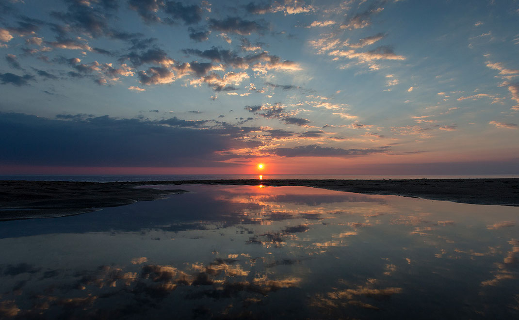 Reflections at a beautiful sunset with light rays and warm colors, north sea, Holland, Netherlands, 1280x789px