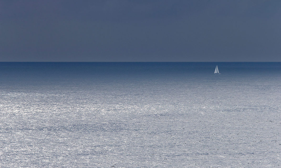 Sailing boat with white sails in the blue Atlantic Ocean with endless horizon, Portugal, summer, 1280x765px