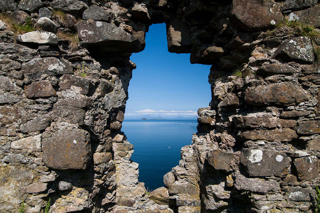 Hole in a wall of a Duntulm castle ruin with blue ocean and seabirds in the back, 1280x853px