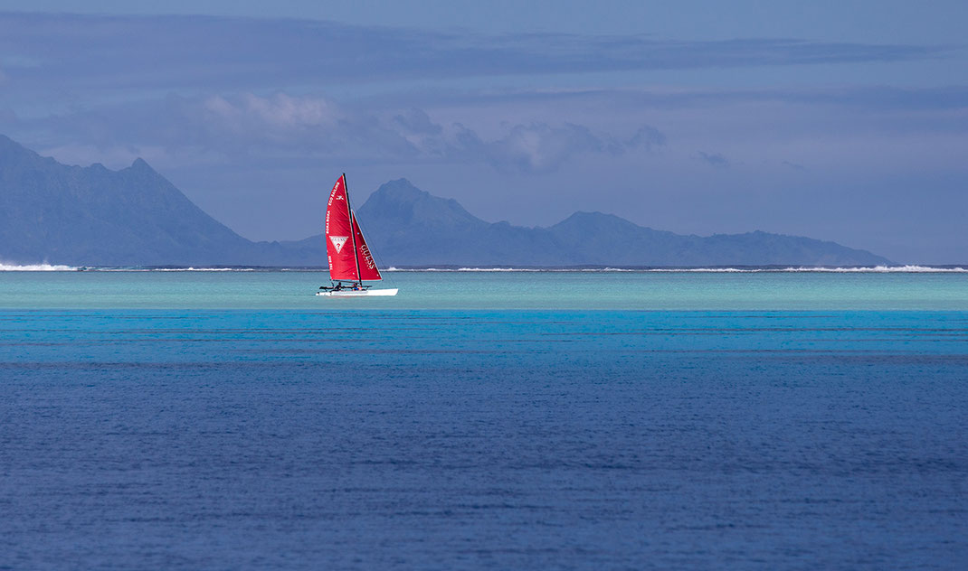 Beautiful turquoise water and mountains with a catamaran and red sails, Bora Bora, South Pacific, French Polynesia, 1280x756px