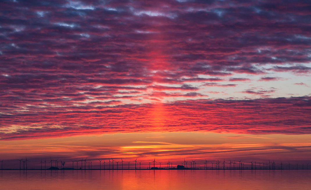 Sun rays in amazing colors with red and purple during sunset at the north sea coast and wind energy installations in the back, Ost-Friesland, Germany