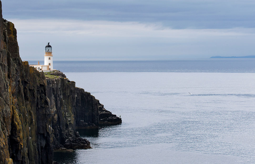 Neist Point Lighthouse on a cliff with ocean and fisherman and seagull, isle of Skye, Scotland, 1280x823px