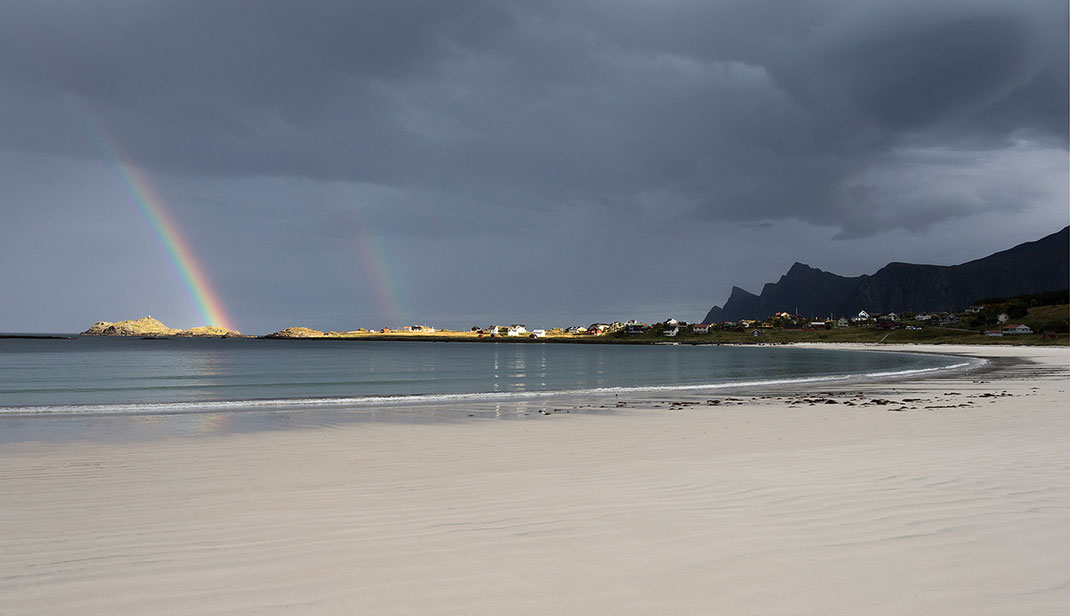 Beautiful light with rainbows at a white ocean beach with dark mountains, Lofoten Islands, Norway, 1280x737px