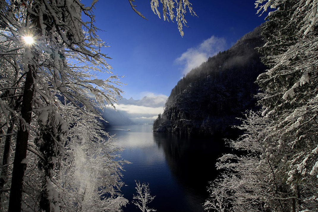 Blue skies with sun and fresh white snow at beautiful Malerwinkel, Königssee and boat, Alpes, Bavaria, Germany, Europe
