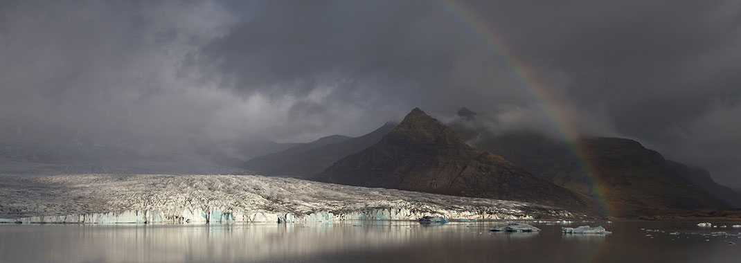 Rainbow at a glacier lagoon with icebergs floating and mountains in the background, Austurland, Iceland