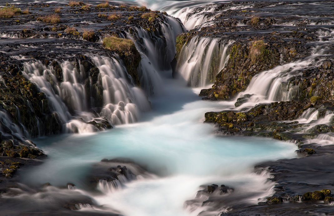 Beautiful hraunfossar waterfall with nice cascades of water in blue and white colors, long exposure photo, Iceland