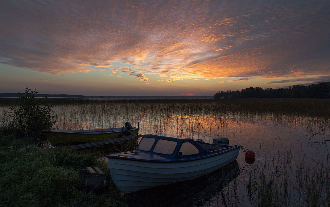 Sunrise at a lake in Gaevle, Sweden, Scandinavia with two boats and warm colors in the sky