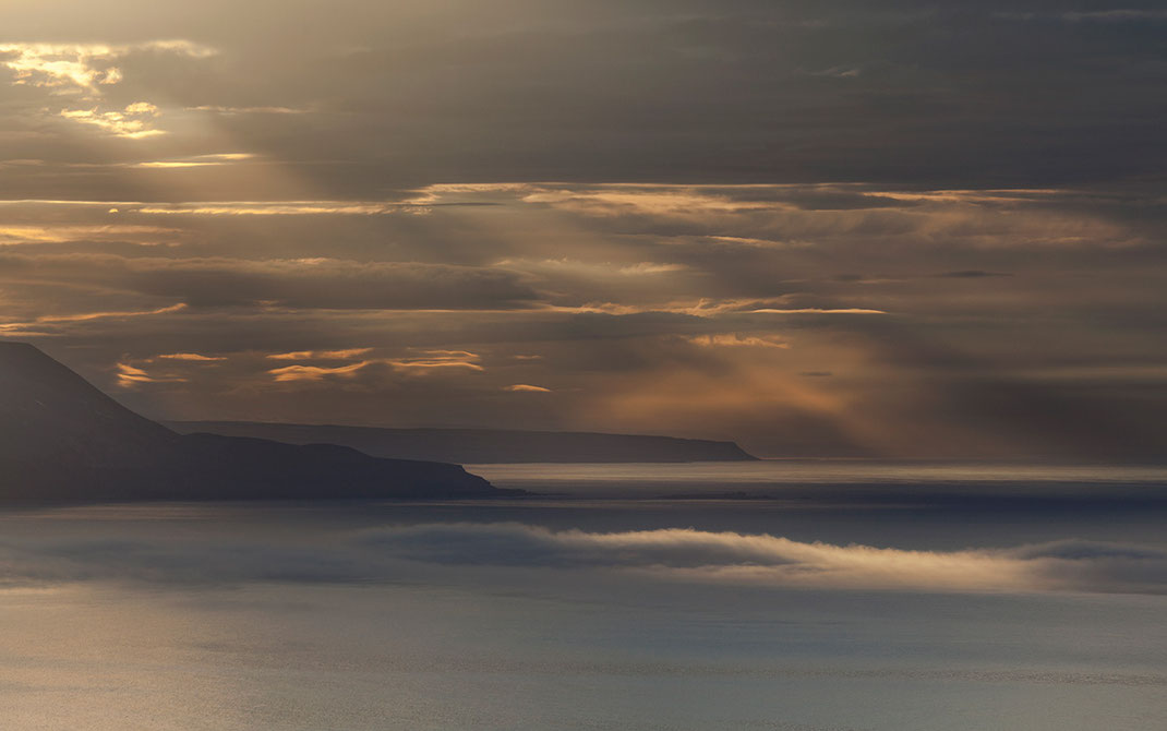 Layers of clouds and sun rays during sunset in the east coast fjords, Iceland