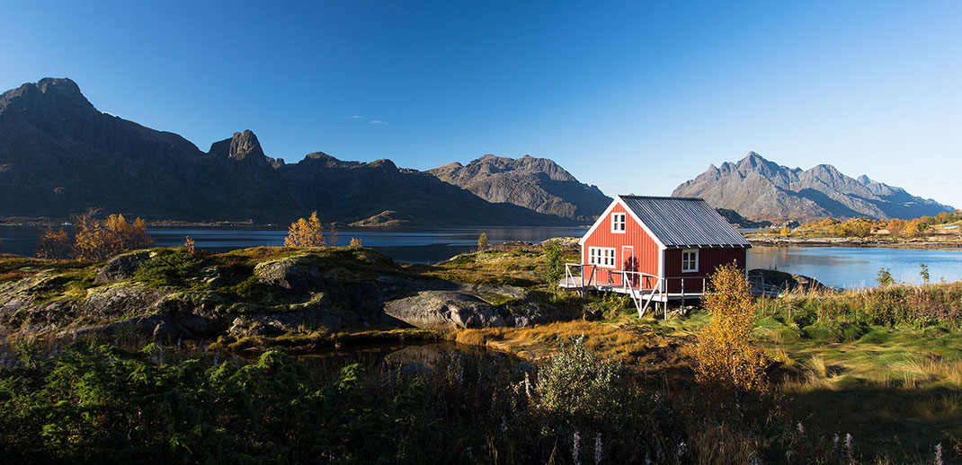 Red traditional house in beautiful landscape with Troll Fjord and Mountains at sunshine, Lofoten Islands, Norway, 1280x620px