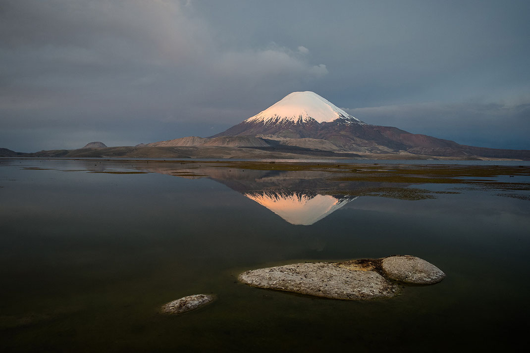 Vulcan Parinacota with snow cover in sunset light glow and reflecting in a lake, Putre, Parque Lauca, Chile, 1280x853px