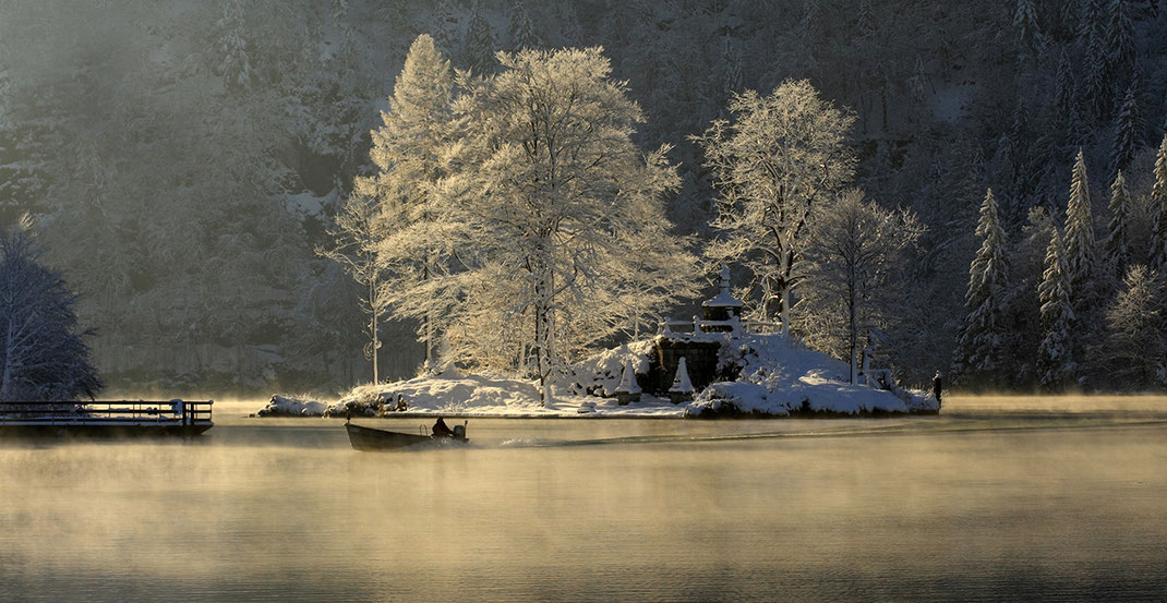 Morning fog at the beautiful Koenigssee with a boat at freezing temperatures, Alpes, Bavaria, Germany
