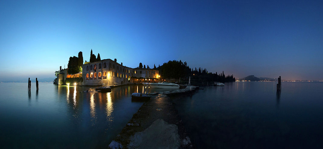 Illuminated classical building with pier and boats at Lago di Garda, lake in Italy at night, 1280x750px
