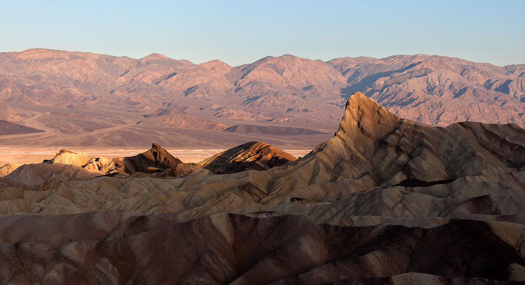 First sunshine at the rocks of Zabriskie Point with the Sierra Nevada in the back, Death Valley National Park, California USA, 1280x695px