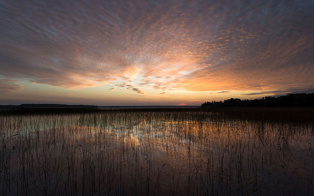 Colorful sunrise at a lake in Gaevle, Sweden with orange and purple colors in the sky