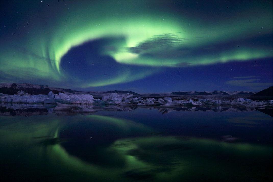 Beautiful Northern Lights, Aurora Borealis reflecting in Jokulsarlon Lagoon, floating Icebergs, Iceland