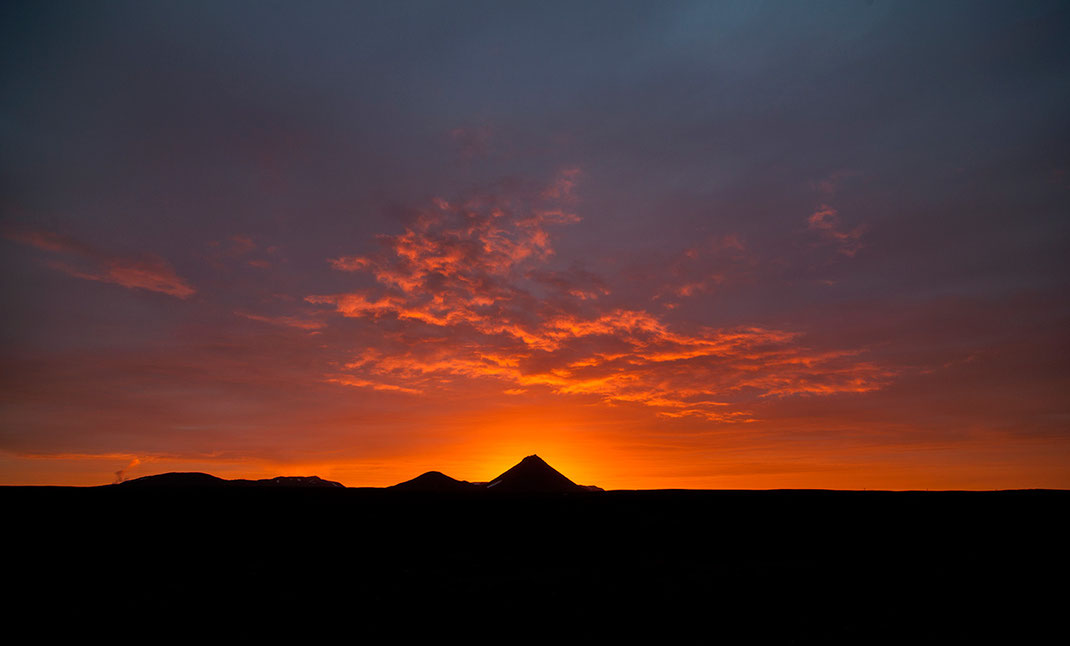 Dramatic and beautiful sunset with intense red colors and silhouettes of mountains at midnight, North Iceland
