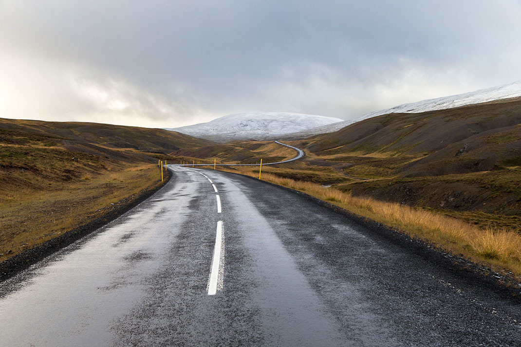 Winding road leading into snowy mountains, countryside, Iceland
