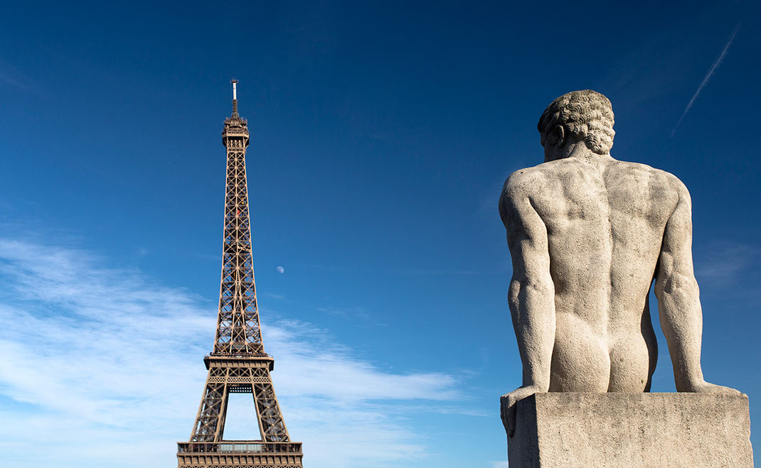 Male stone sculpture with view to the Eiffel Tower and the moon with beautiful blue skies, Musee de l' Homme, France