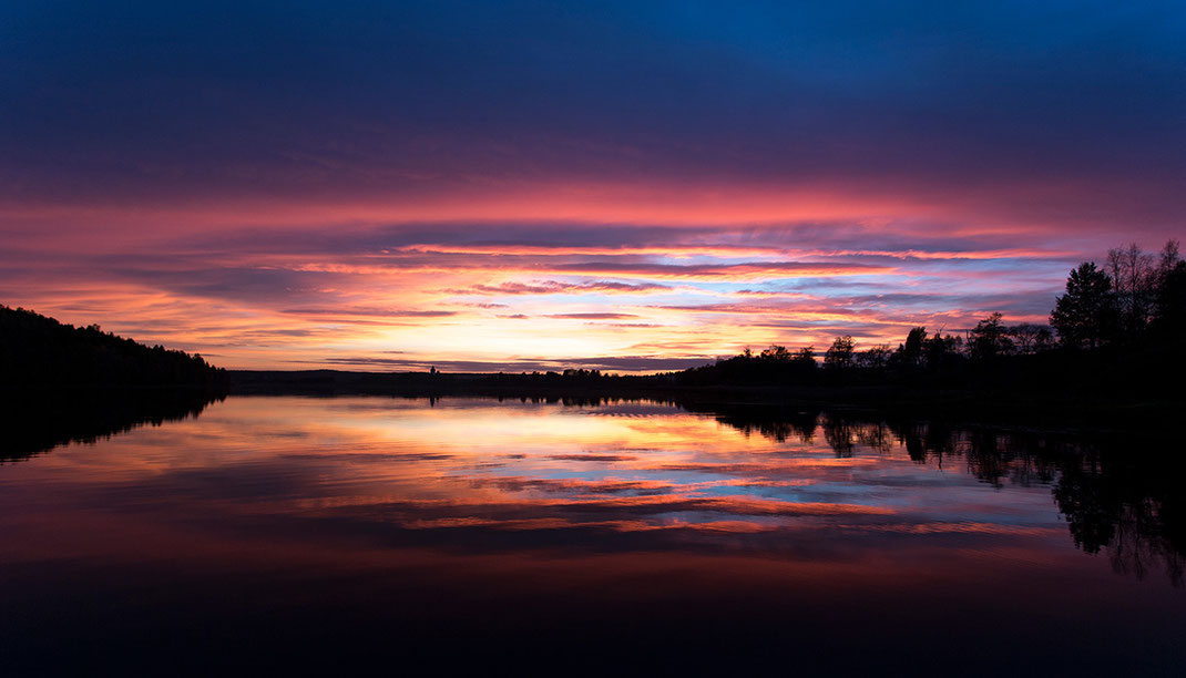 Last beautiful colors red and purple with reflections in a lake at sunset, Hundiksvall, Sweden, Scandinavia
