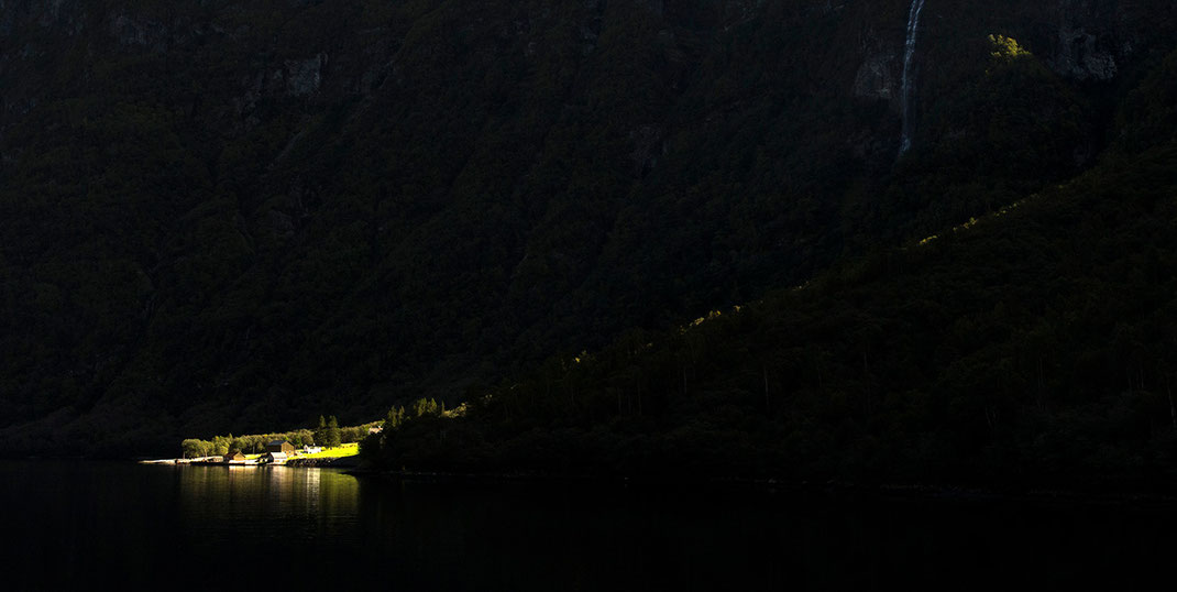 Last light on a farm in beautiful Narrow Fjorden landscape with mountain and waterfall, Sognefjord, Norway, 1280x644px