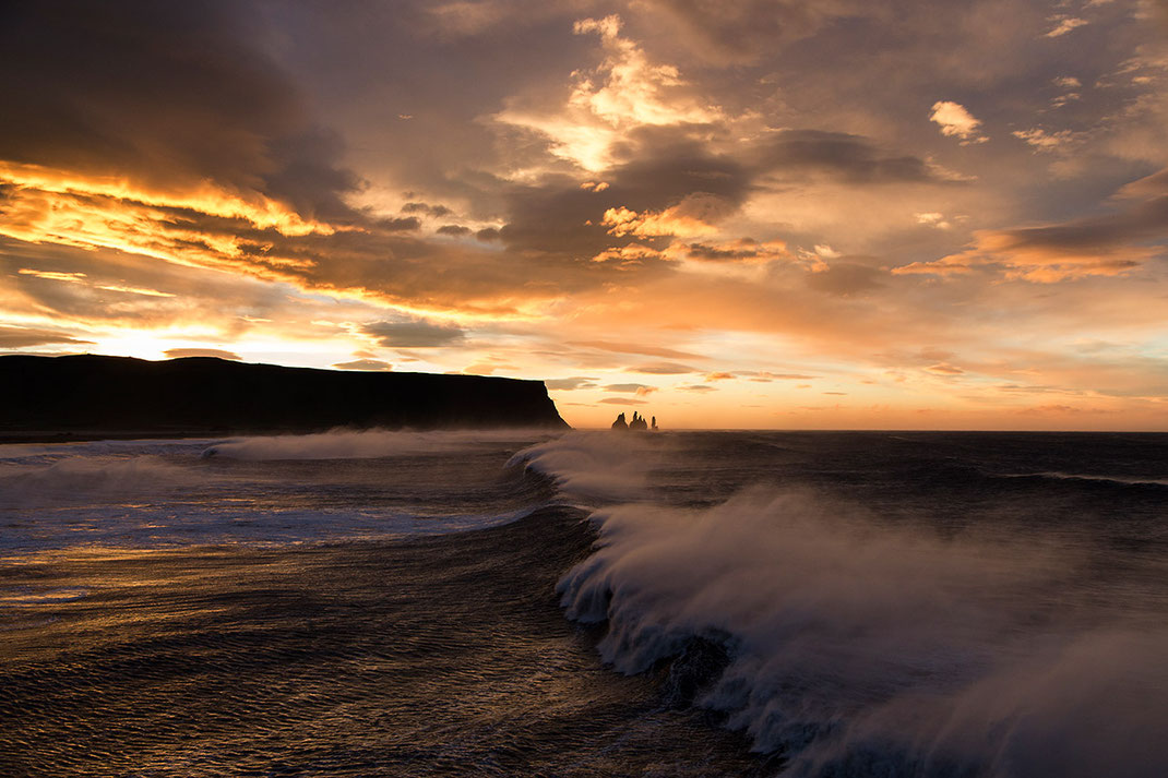 Beautiful red and orange sunrise with huge waves at the Atlantic Ocean at Dyrholaey, Vik i Myrdal, Iceland
