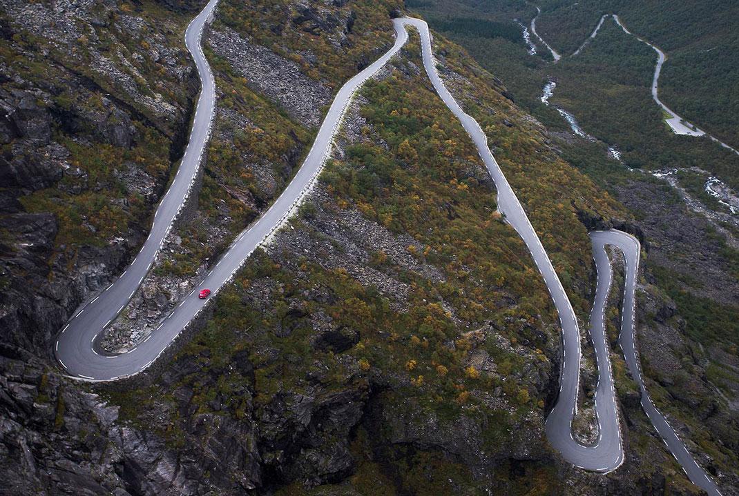 Red car on winding serpentine road, Trollstigen viewing point, mountain area, Norway, 1280x860px