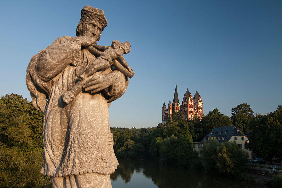 Statue at river Lahn with romanic Limburger Dom in warm evening light, Limburg, Hessen, Germany, Europe