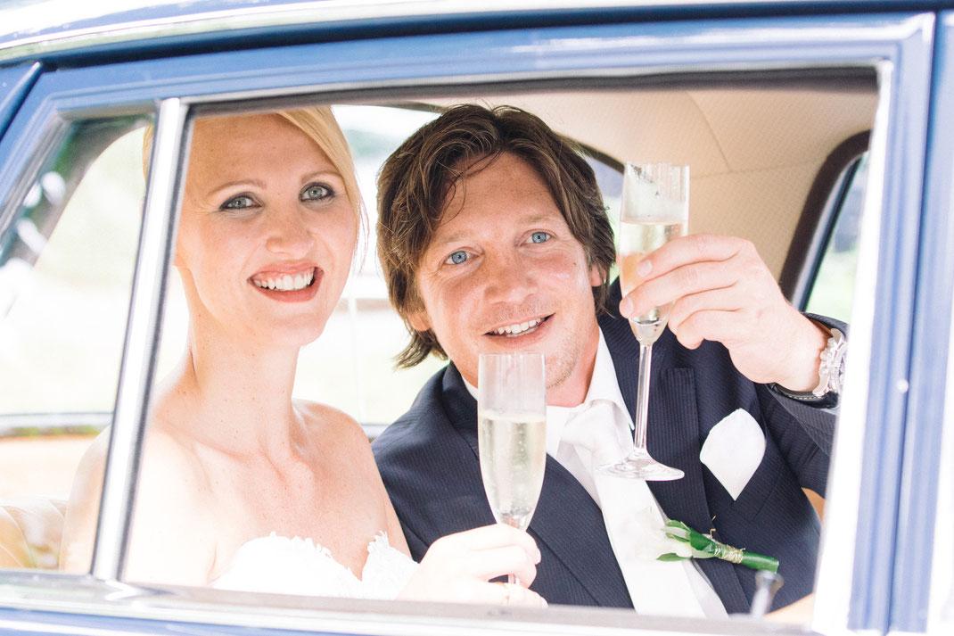Brautpaar im Brautwagen mit Sektgläsern