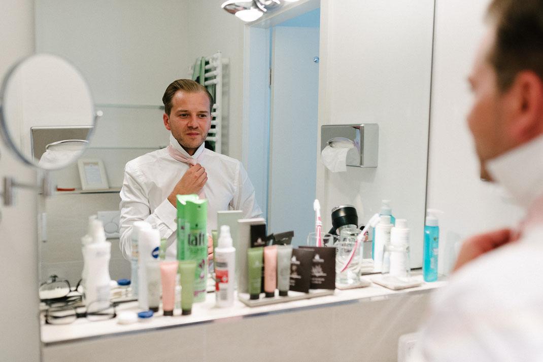 Bräutigam blickt in den Spiegel