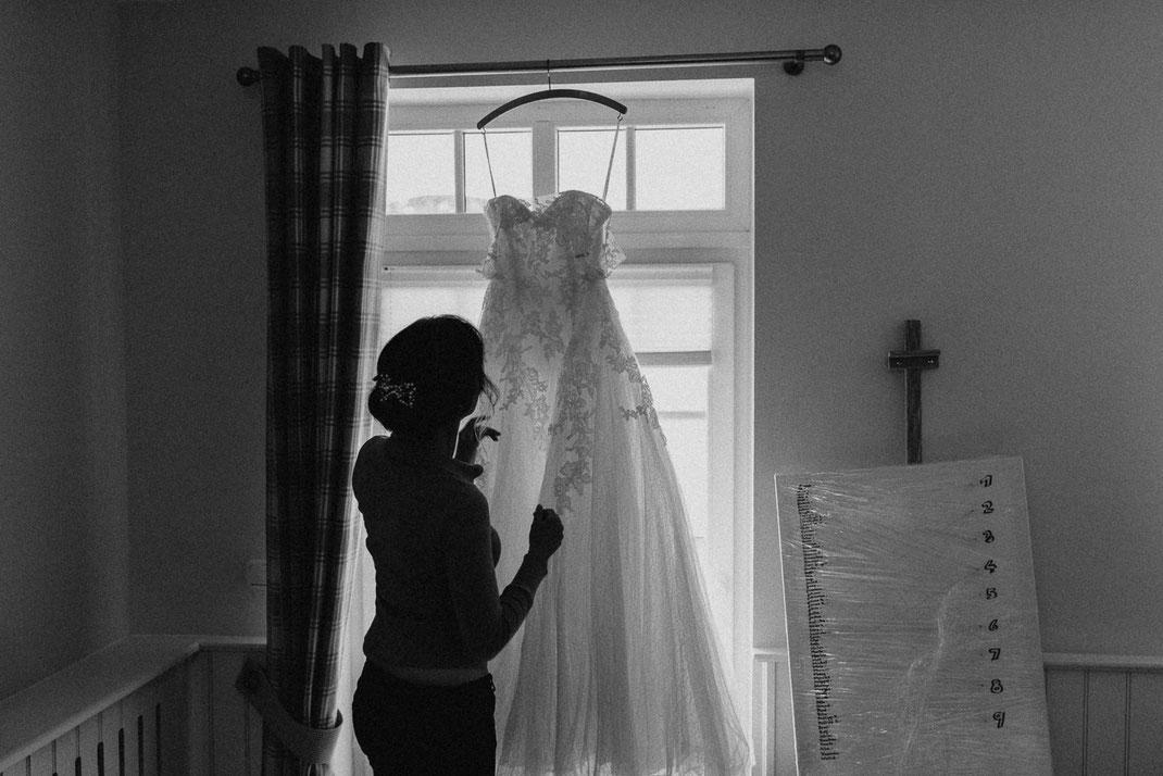 Braut schaut auf Hochzeitskleid