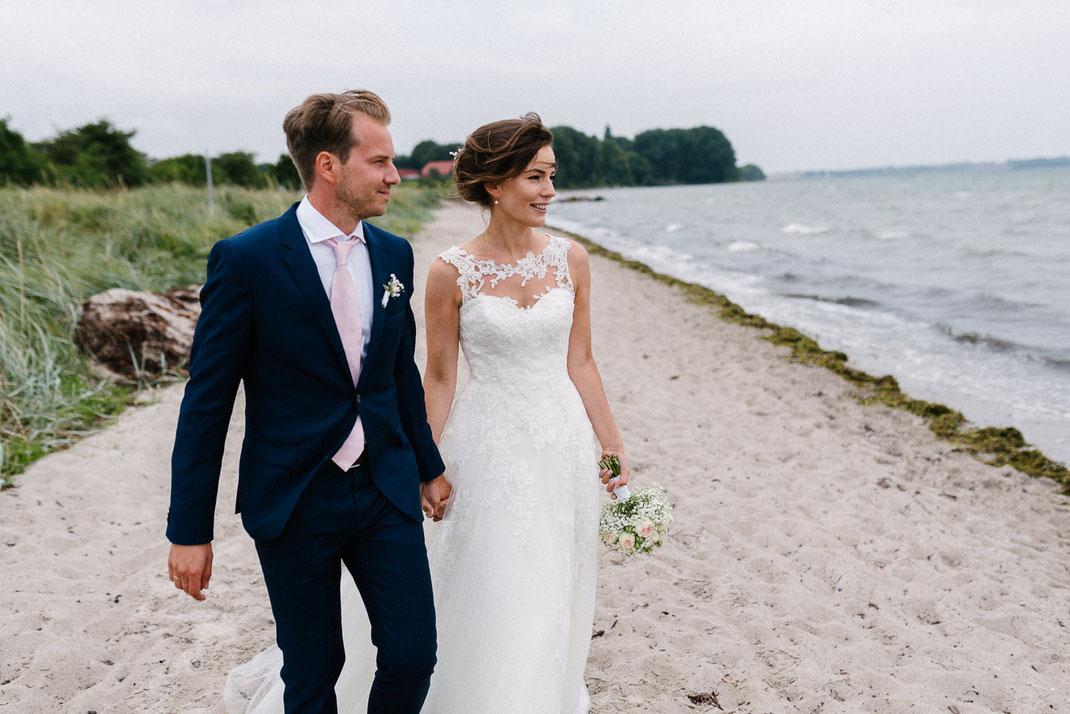 Paar geht am Strand Ostsee Blick nach Dänemark