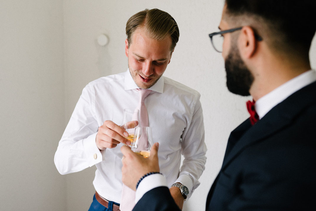 Männer stoßen mit Whisky an