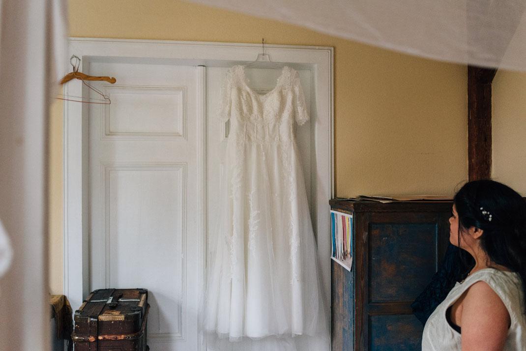Braut blickt auf ihr Kleid an der Tür