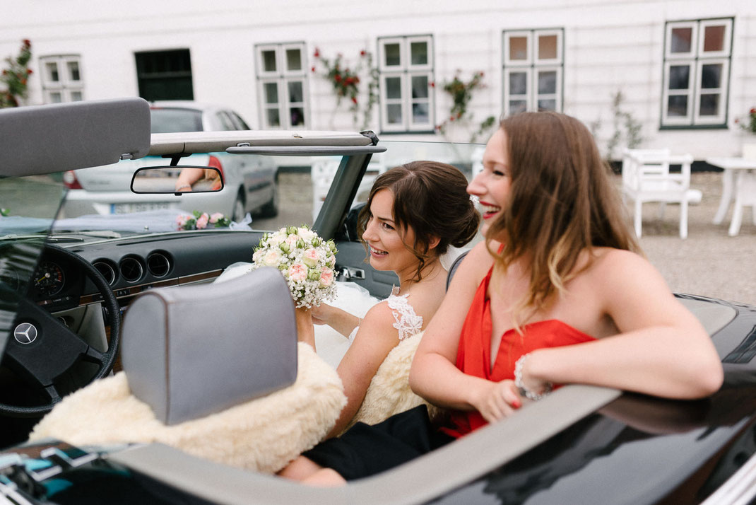 Braut und Trauzeugin im Auto vor Schloss Glücksburg