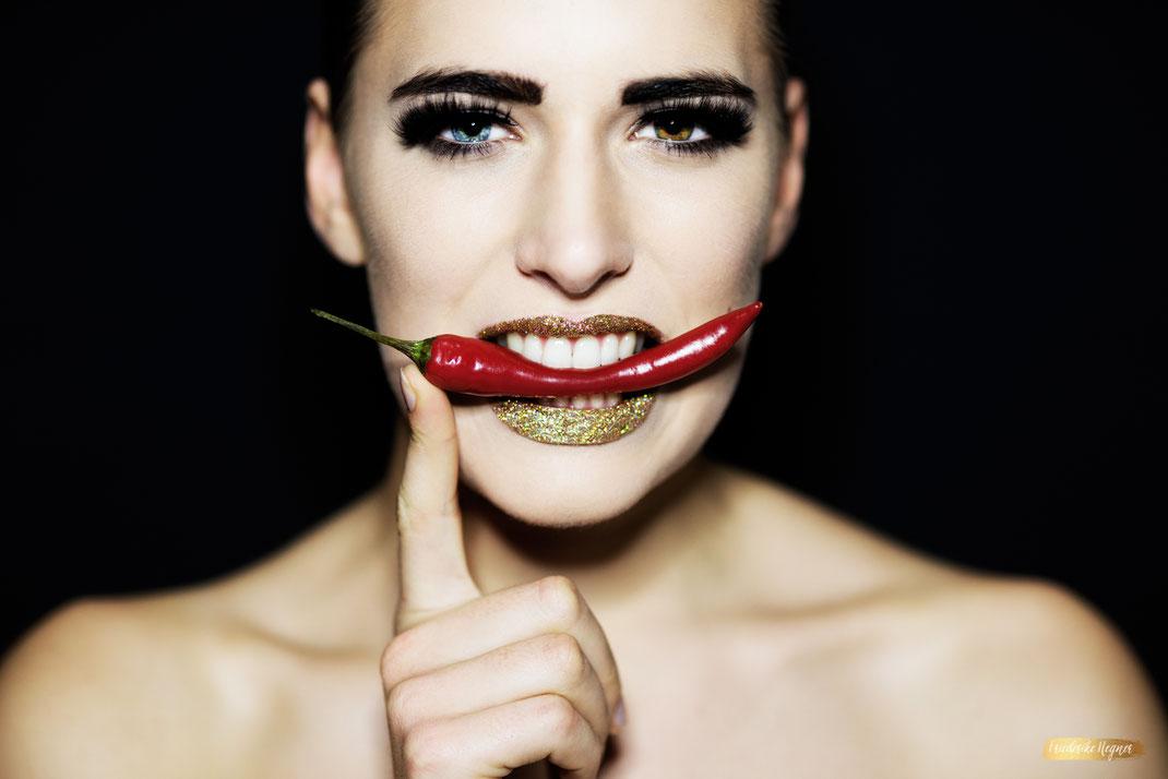 Kampagnenmotiv Edel und Scharf Kühlungsborn - Frau mit einer Chili-Schote im Mund