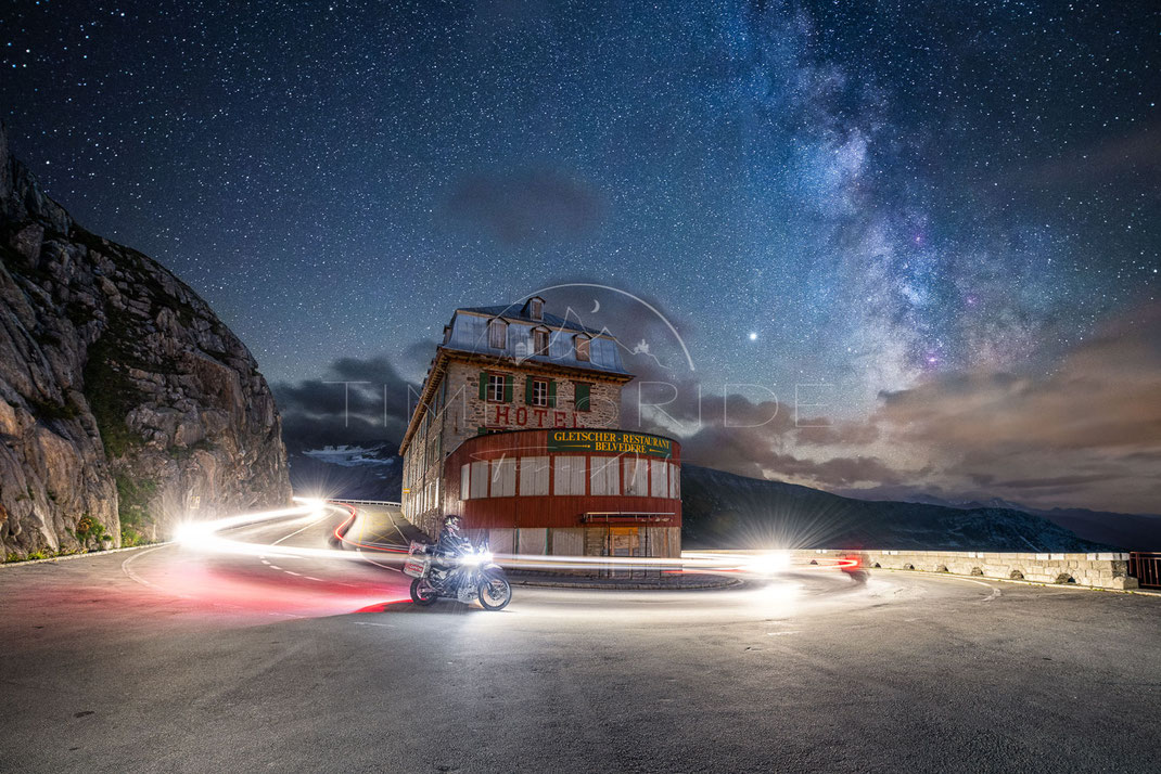 Riding a motorcycle under the milkyway at the famous hotel belvedere (Furkapass in Switzerland)
