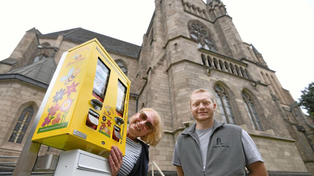 Pfarrgemeinderätin Rita Osowski und Imker Raffael Lukasczyk freuen sich, dass es nun einen Bienenfutterautomaten gibt. Er ist gefüllt mit Kugeln voller Wildblumensamen. (WAZ-Foto: Oliver Müller / FUNKE Foto Services)