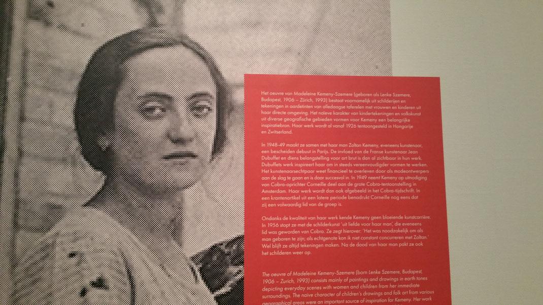 Op de foto is een portret van een droevig uitziende vrouw te zien: Madeleine Kemeny Szemere. Naast haar hoofd is een rood vak aangebracht met daarop haar levensbeschrijving in witte letters.