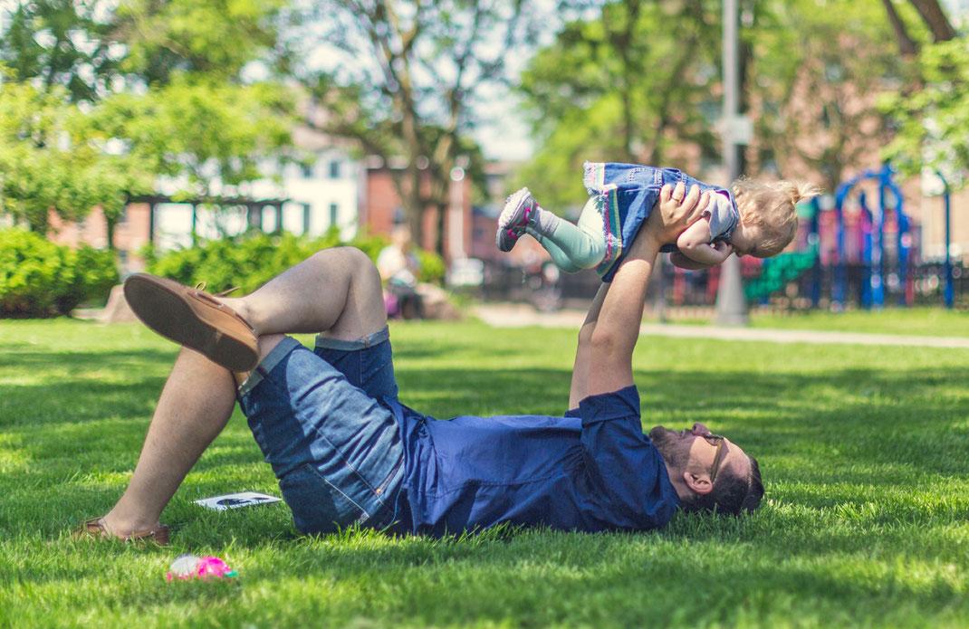 Vater liegt mit Rücken auf Wiese und hält sein Kind spielend in die Luft.